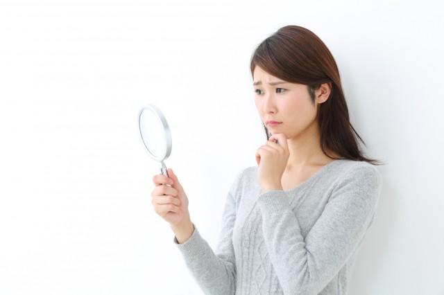 虫眼鏡と顔をしかめる女性