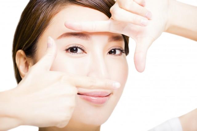 指で目元を囲っている笑顔の女性